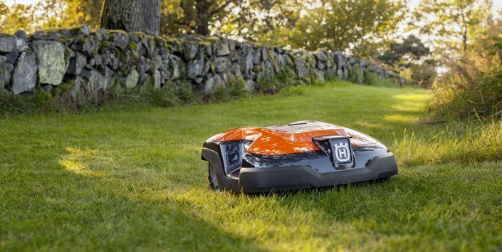 Робот газонокосилка Husqvarna стрижет траву на газоне фотография