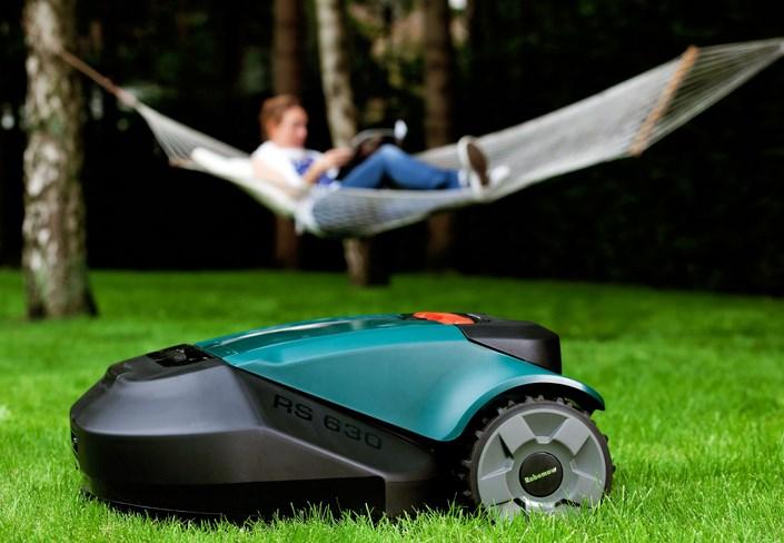 робот газонокосилка robomow за работой на участке возле дома